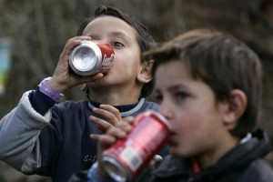 Children of Kosovo Ashkalli minority drink during ribbon-cutting ceremony for their new home in central Kosovo