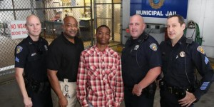 Jamal pictured with police officers, after saving Officer  Franklin Foulks