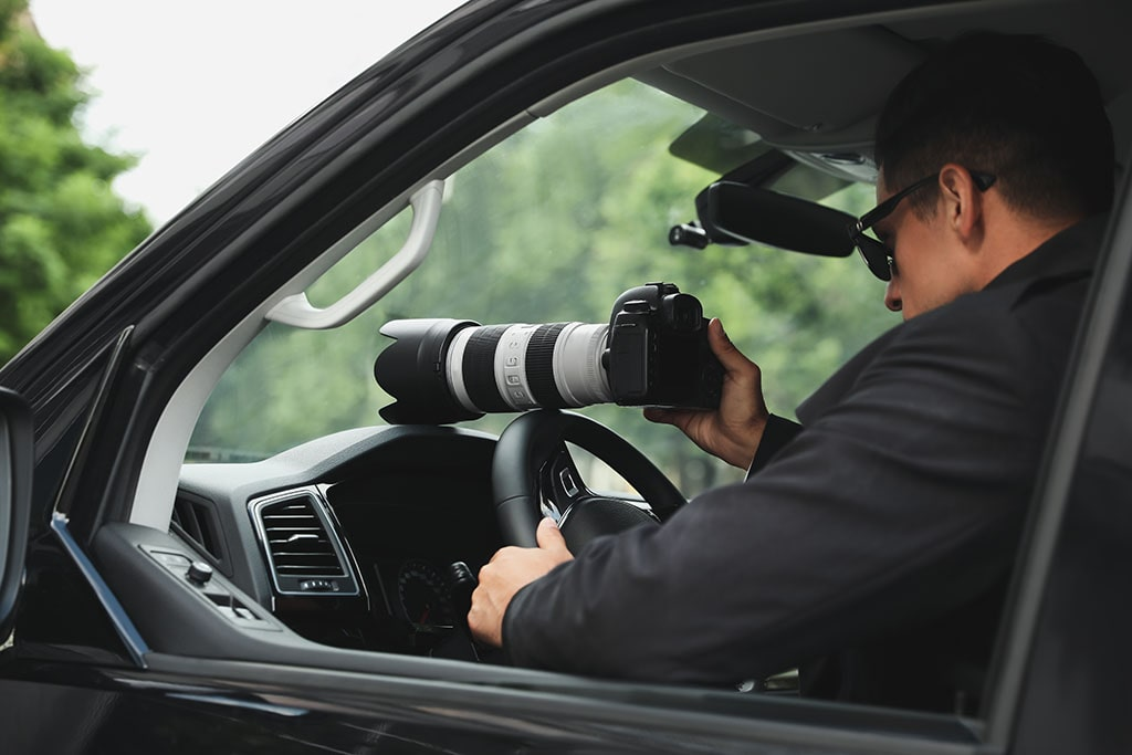 Policeman uses long lens to spy into the distance from his car