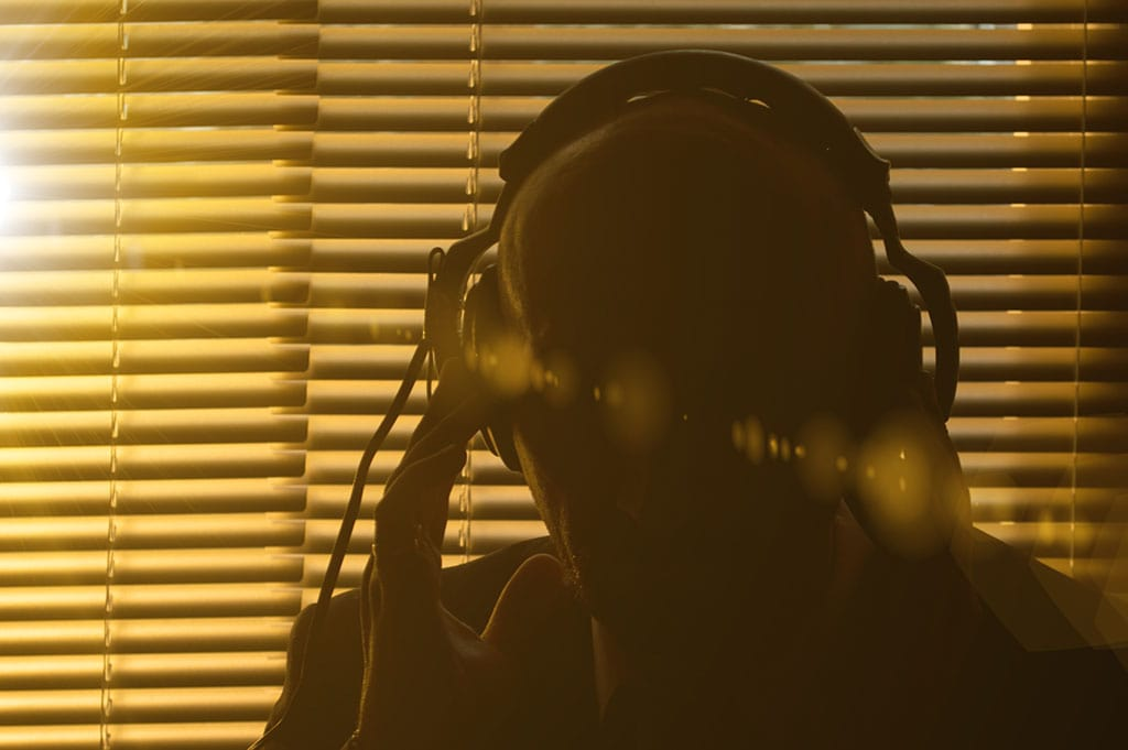 Secret policeman listens in using headphones behind blinds in shadowy background to use in Covert Human Intelligence Sources Act