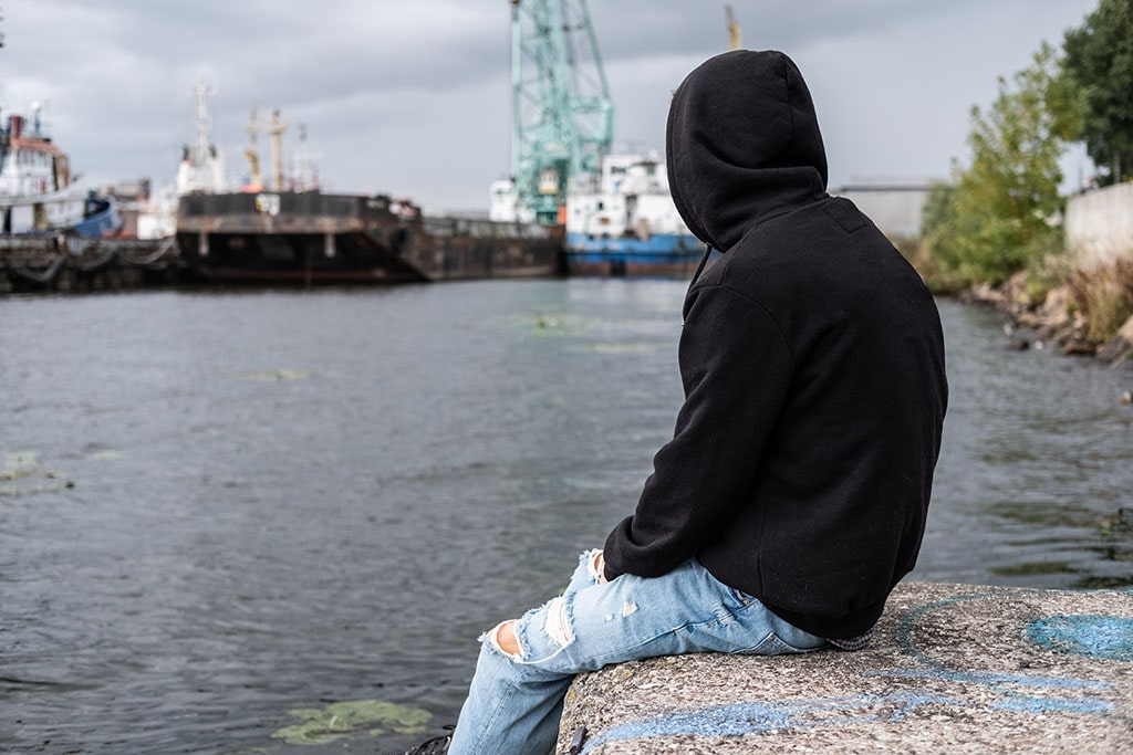 Young man in hoodie sits near waterway looking out into the distance