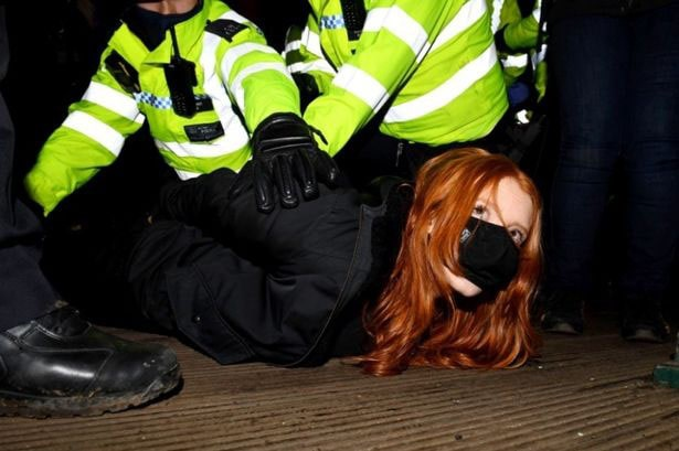 Police in yellow jackets tackle red hairded Patsy Stevenson who is lying on the ground