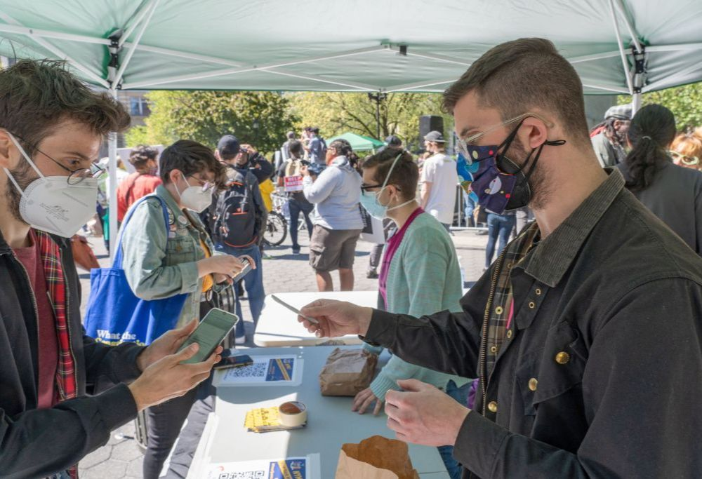 Masked volunteers hand out marijuana joints under a canopy