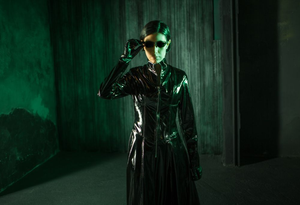 Female hacker from the matrix dressed in shiny black leather with a green and black background